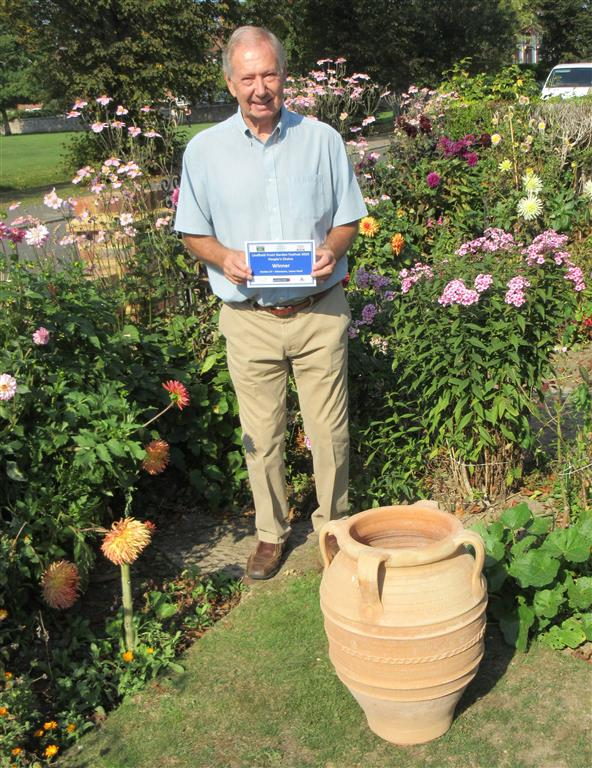 Ron Harris in his garden with prize donated by Pots and Pithoi